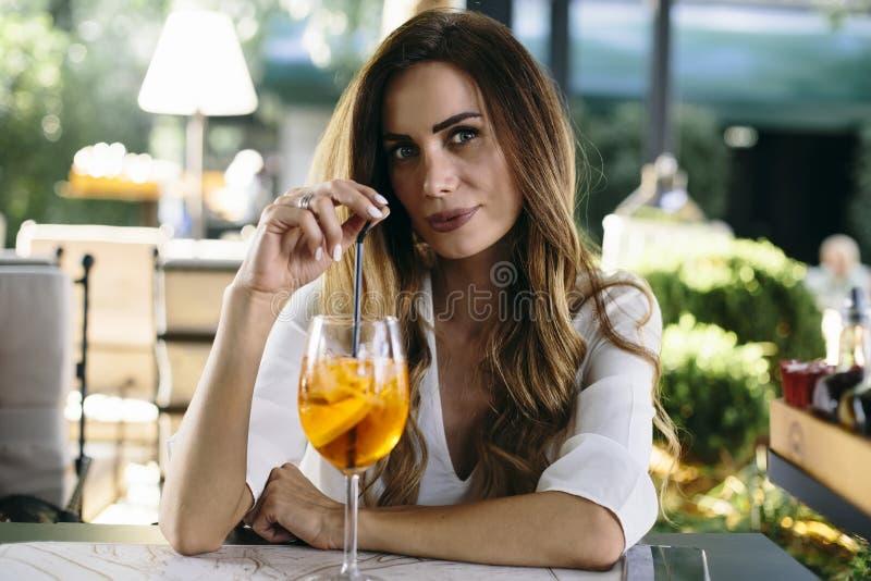 Attraktiv ung kvinna som dricker coctail i det utomhus- kafét royaltyfri fotografi