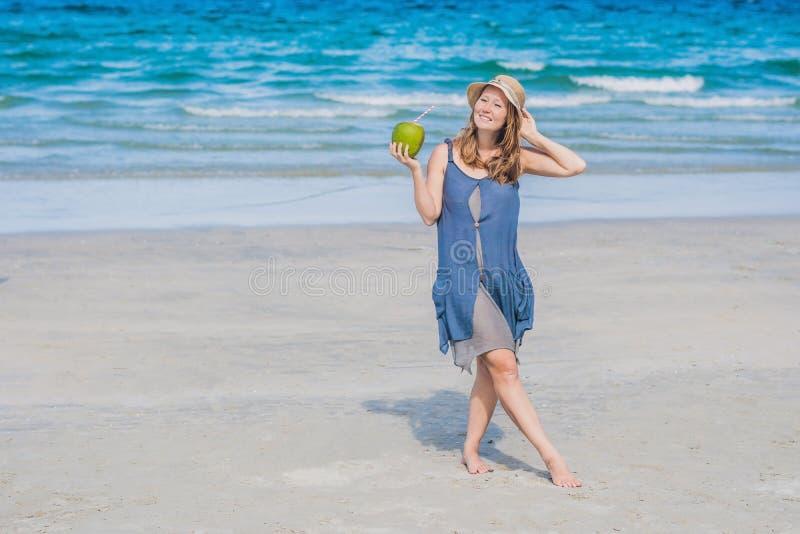 Attraktiv ung kvinna som dricker kokosnötvatten på stranden arkivfoto