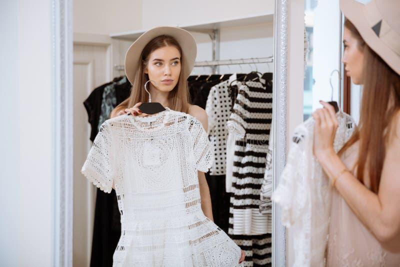 Attraktiv ung kvinna som framme försöker på klänningen av spegeln arkivfoton