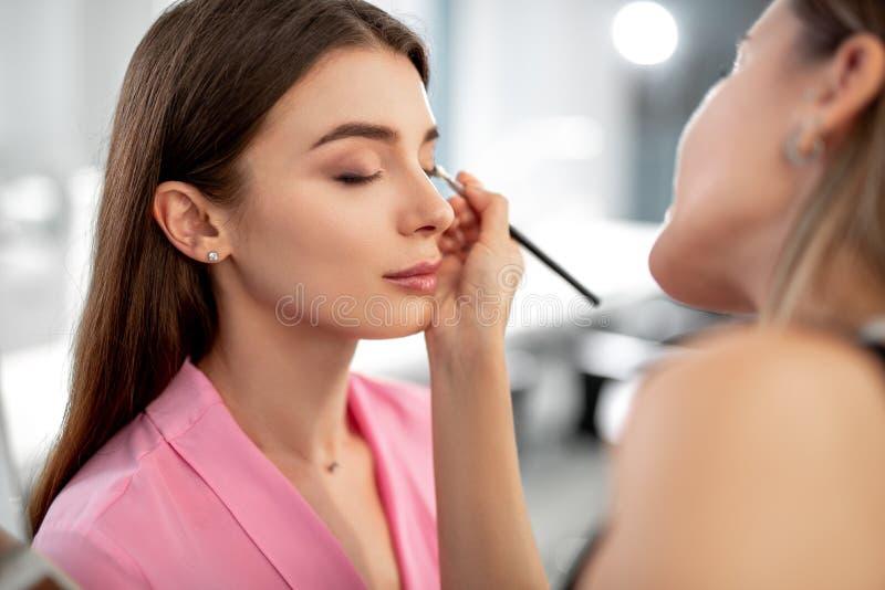 Attraktiv ung kvinna som gör makeup i skönhetsalong fotografering för bildbyråer