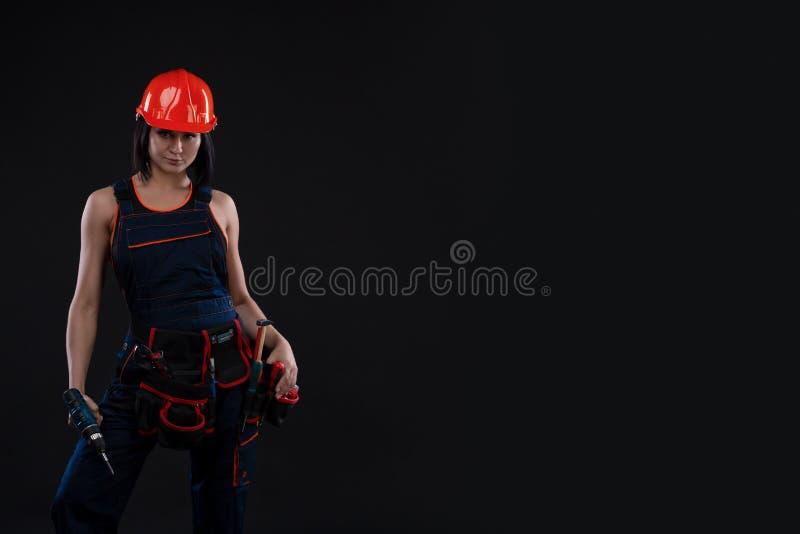 Attraktiv ung kvinna som gör reparationer på svart bakgrund Stående av en kvinnlig byggnadsarbetare Bygga reparationsbegrepp kopi royaltyfria bilder