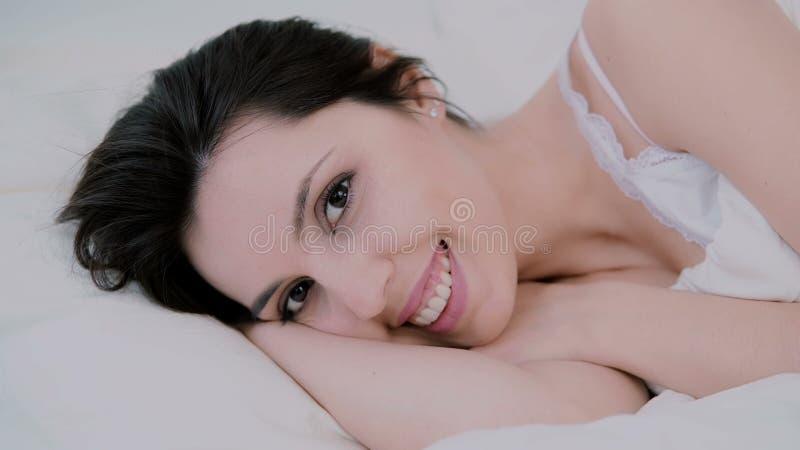 Attraktiv ung kvinna som hemma vaknar upp i säng Flickan ser till kameran och gulliga leenden Ny och lycklig kvinna i morgon royaltyfri bild