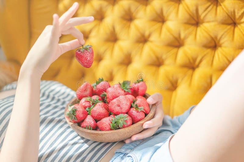 Attraktiv ung kvinna som l?gger p? soffan i en hem- vardagsrum f?r familjrum som ?ter den nya jordgubben royaltyfria foton