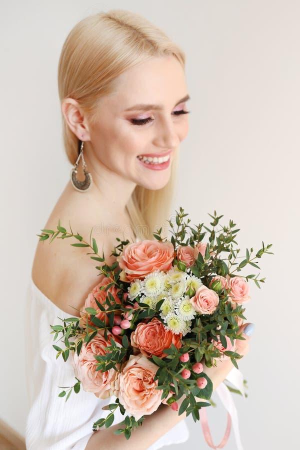 Attraktiv ung kvinna som poserar ?ver gr? bakgrund med blommor royaltyfria foton