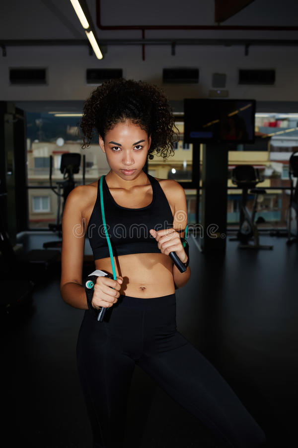 Attraktiv ung kvinna som poserar med konditionexpanderen på idrottshallen arkivbilder