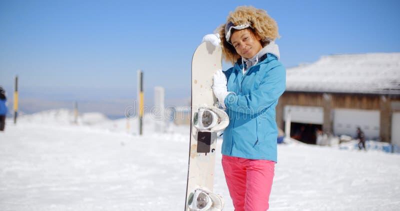 Attraktiv ung kvinna som poserar på en skidasemesterort royaltyfri bild
