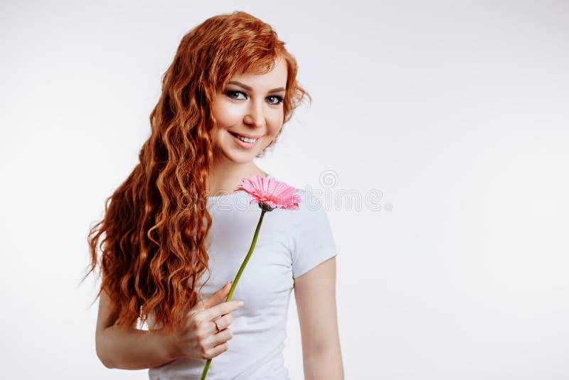 Attraktiv ung kvinna som rymmer en blomma i henne händer royaltyfria foton