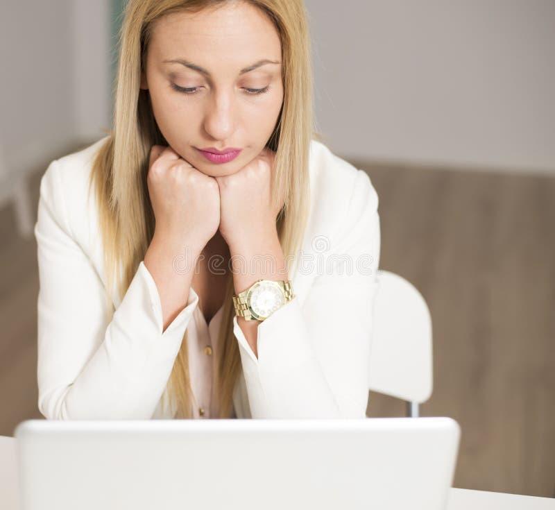 Attraktiv ung kvinna som ser datorskärmen royaltyfri fotografi