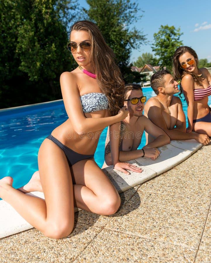 Attraktiv ung kvinna som solbadar vid pölen i bakgrunden av hans vänner arkivfoton