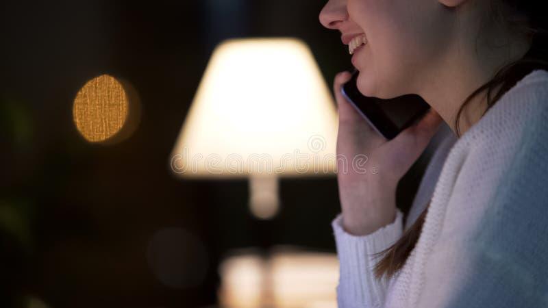 Attraktiv ung kvinna som talar på smartphonen och ler, aftonkafé, närbild royaltyfri foto