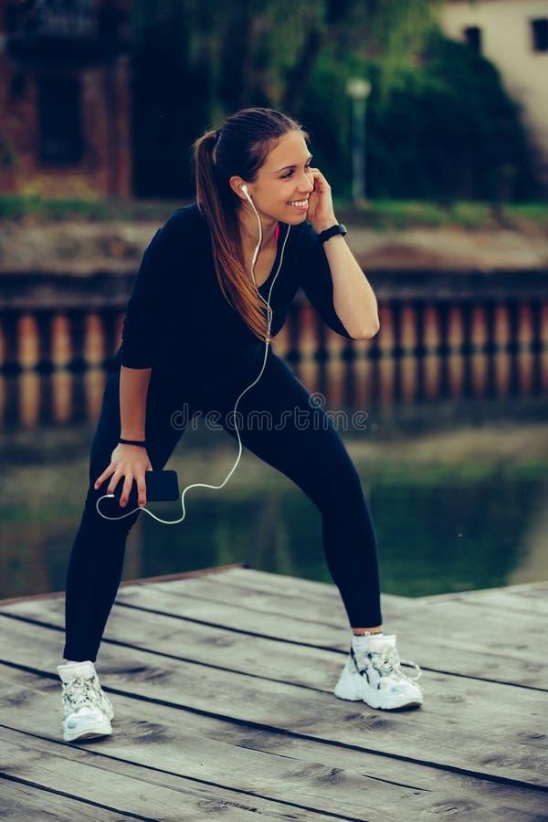 Attraktiv ung kvinna som tar avbrottet, når att ha joggat, medan lyssna till musik på hennes smarta telefon arkivbild