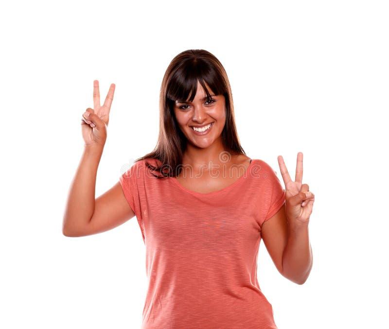 Attraktiv ung kvinna som visar dig segertecknet royaltyfri bild