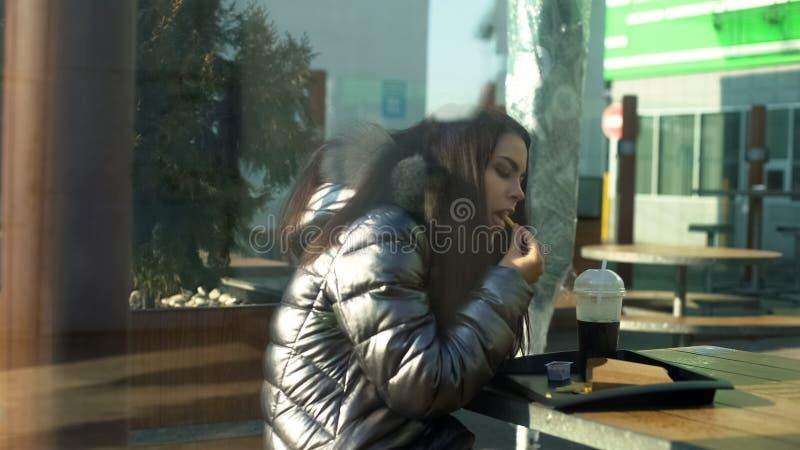 Attraktiv ung kvinnlig som ?ter franska sm?fiskar i kantin, snabbmatmellanm?l, lunch royaltyfria foton