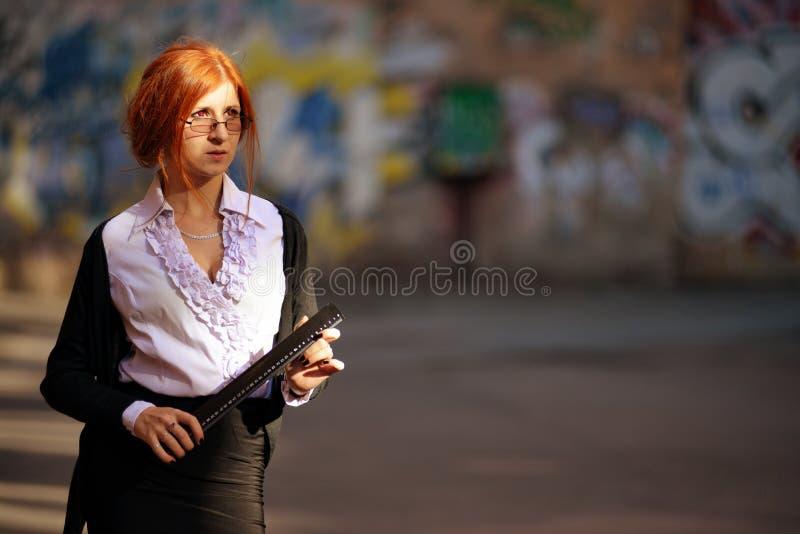 Attraktiv ung lärarekvinna med den plana linjalen mot stads- sikt arkivfoto
