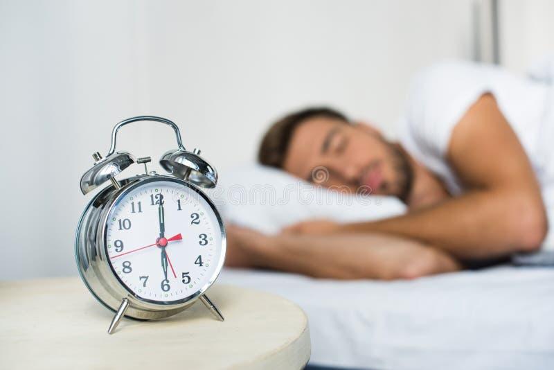 Attraktiv ung man i den vita t-skjortan som sover i säng med ringklockan på hans royaltyfri foto