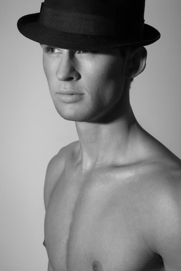 Attraktiv ung man i hatten som bort ser. Svartvitt royaltyfria foton