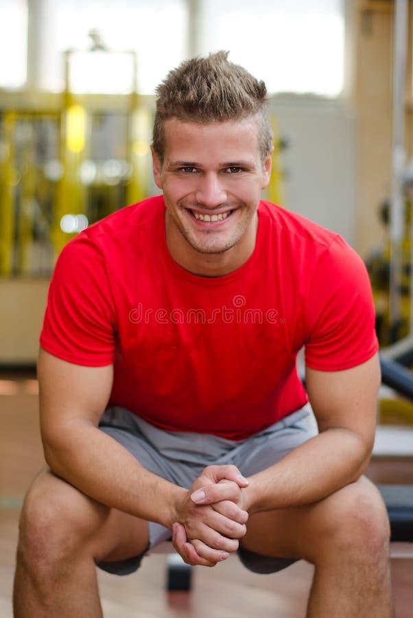 Attraktiv ung man i idrottshallsammanträde på bänken som ler arkivbilder