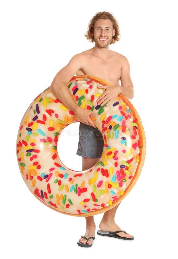 Attraktiv ung man i swimwear med den uppblåsbara cirkeln för munk royaltyfria foton