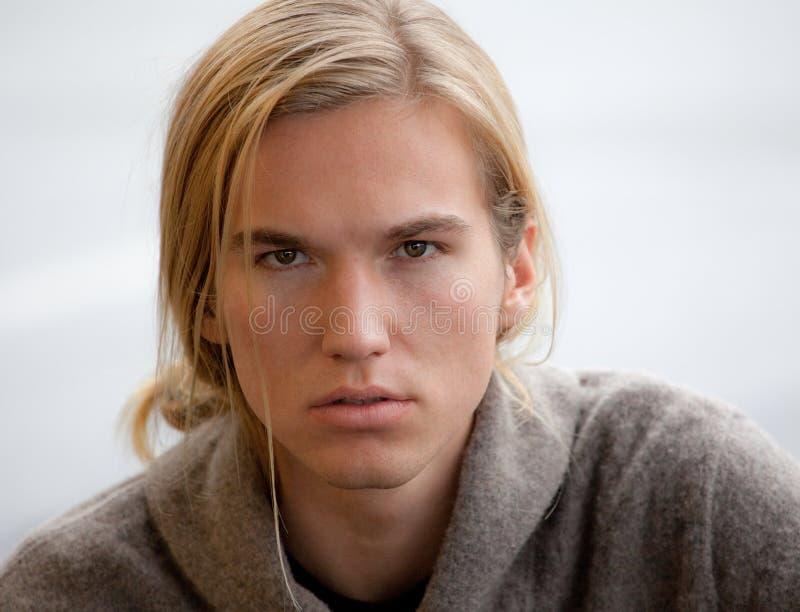 Attraktiv ung man med långt hår fotografering för bildbyråer