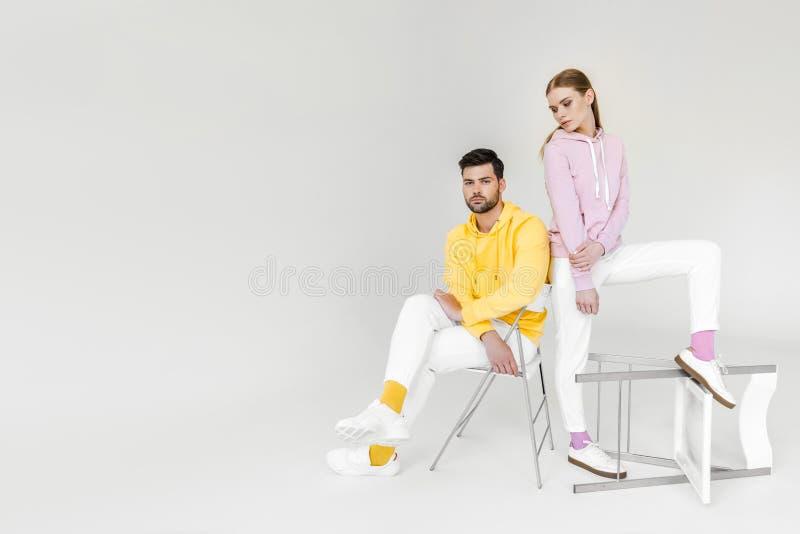 attraktiv ung man och kvinnliga modeller i färgrika hoodies arkivfoton