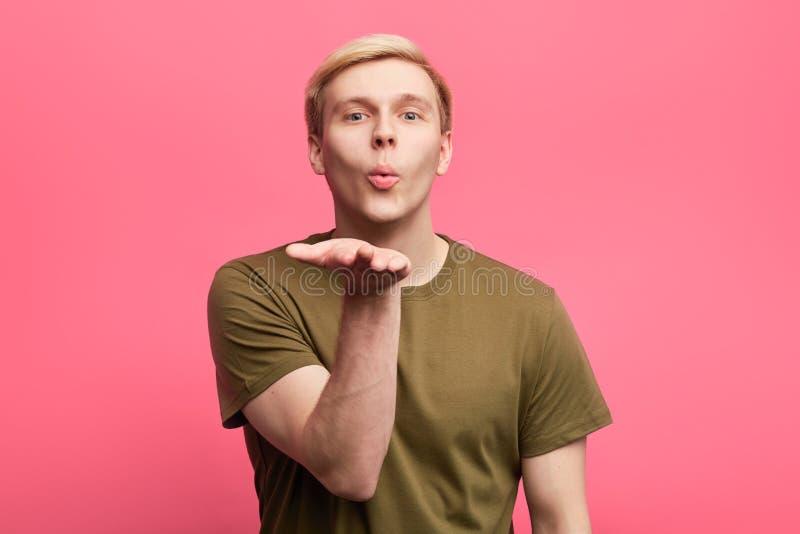 Attraktiv ung man som blåser kyssen till hans vän M?nskligt ansikts- sinnesr?relsebegrepp arkivfoton