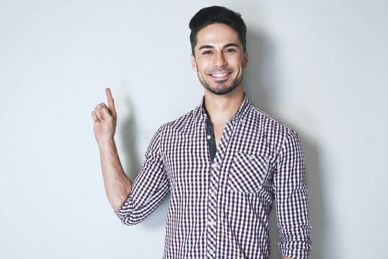 Attraktiv ung man som gör en gest med pekfingret till väggen royaltyfria bilder