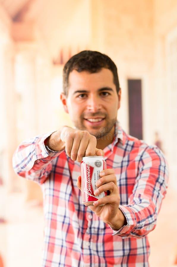 Attraktiv ung man som ler öppna en coca - cola arkivbilder