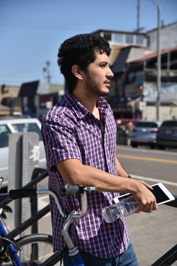 Attraktiv ung man som lutar mot en cykelkugge med en minnestavladator arkivbild
