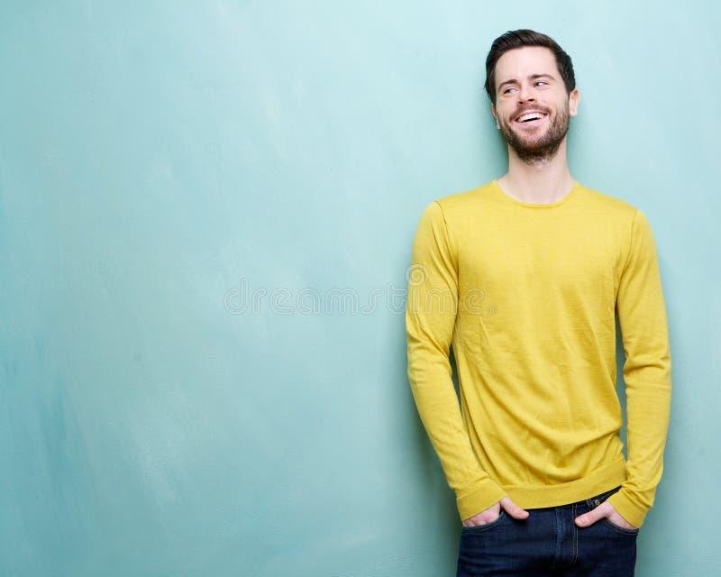 Attraktiv ung man som skrattar mot blå bakgrund arkivfoto