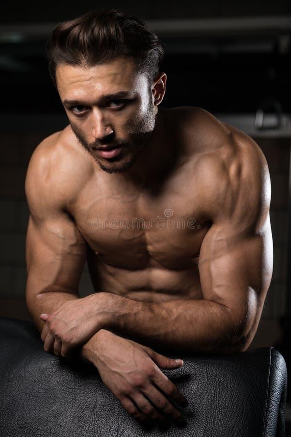 Attraktiv ung man som vilar i den idrottshallAfther övningen royaltyfri foto
