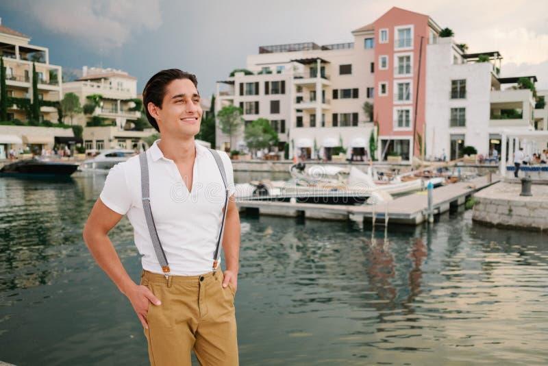 Attraktiv ung modeman i en dräkt mot bakgrunden av porto Montenegro royaltyfri bild