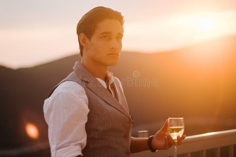 Attraktiv ung modeman i en dräktkvällsmål på terrassen och det vita vinet för drinkar bredvid villan arkivbild