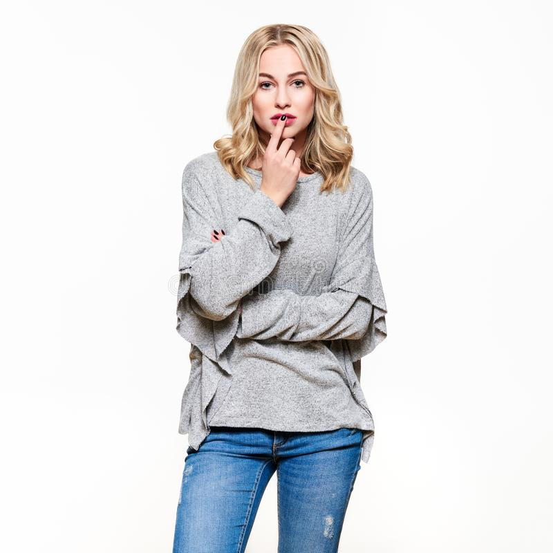 Attraktiv ung säker kvinna som bär tillfällig kläder som tänker, med fingret på kanter som ser kameran royaltyfria foton