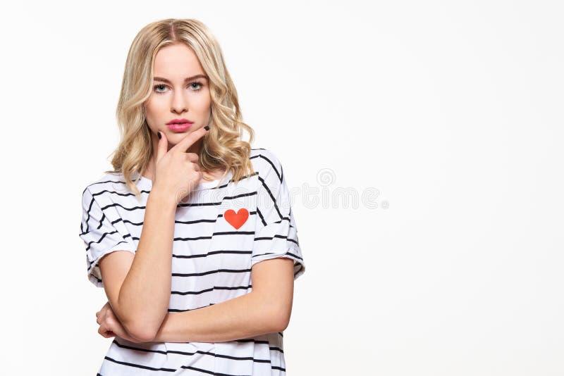 Attraktiv ung säker kvinna som bär tillfällig kläder som tänker, med handen på hakan som ser kameran royaltyfria foton