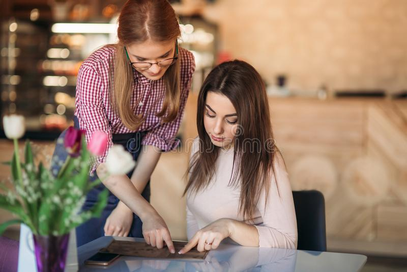Attraktiv ung servitris som använder en minnestavladator för att ta en beställning från en kund i en coffee shop fotografering för bildbyråer