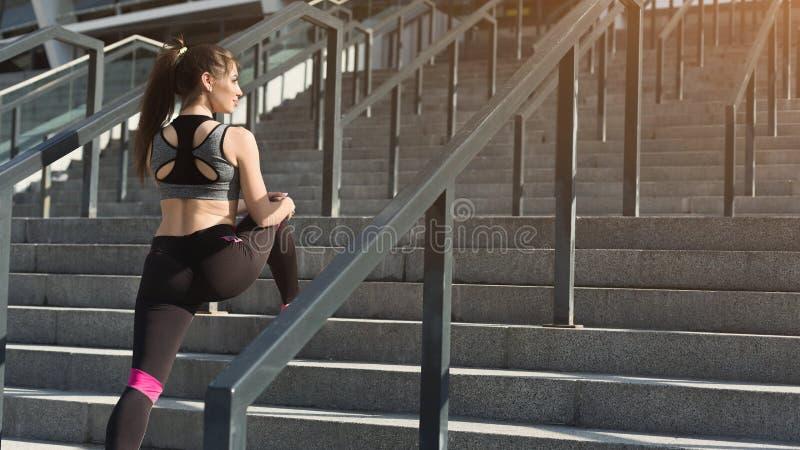 Attraktiv ung sportig kvinna som sträcker på trappa arkivbild
