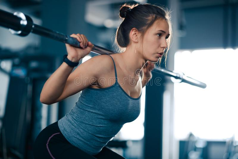 Attraktiv ung sportkvinna som g?r Squats med skivst?ngen i idrottshallen Kondition och sund livsstil arkivbild