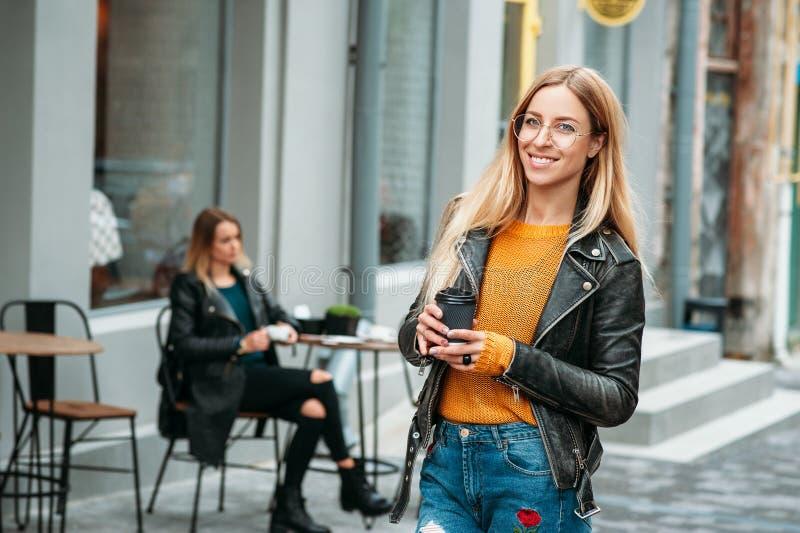 attraktiv ung stilfull kvinna som rymmer en kopp kaffe och ett anseende nära kafét fotografering för bildbyråer