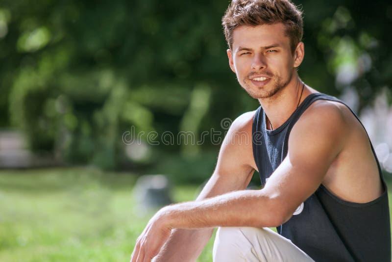 Attraktiv utomhus- stående för ung man arkivbild