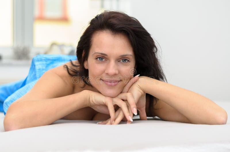 Attraktiv vänlig kvinna som kopplar av på hennes säng arkivbilder