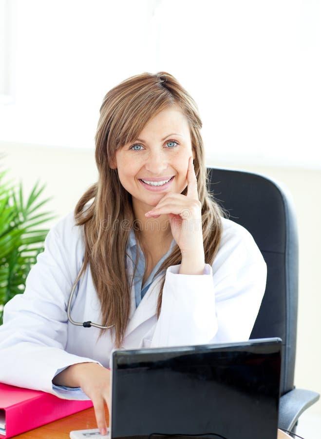 attraktiv working för doktorskvinnligbärbar dator arkivfoto