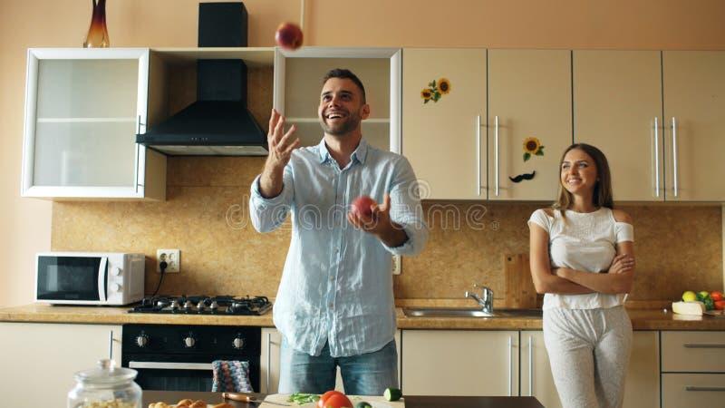 Attraktiva älska par som har gyckel i köket Den stiliga mannen jonglerar med äpplen för att imponera hans flickvän fotografering för bildbyråer