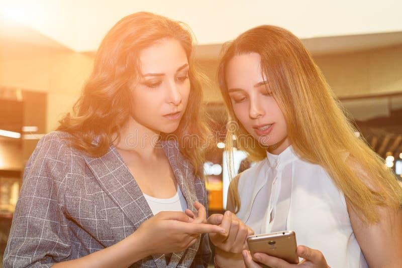 Attraktiva affärskvinnor är tala och se telefonen Ståendefotografi inomhus arkivbild