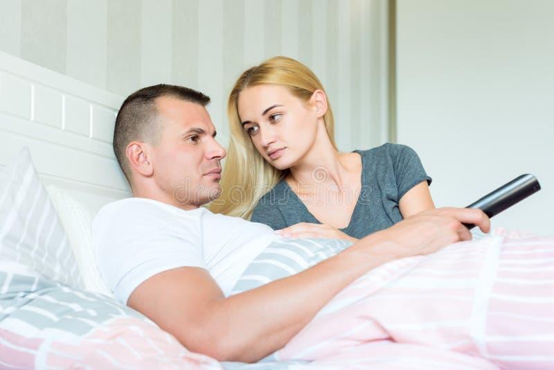 Attraktiva caucasian par i säng Man hållande ögonen på tv, kvinnan som ser lovingly honom och att hoppas för att fånga hans uppmä royaltyfria foton