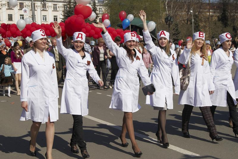 Attraktiva flickor i enhetliga sjuksköterskor ståtar på arkivbild