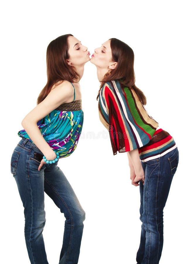 attraktiva flickor som kysser två barn royaltyfri bild