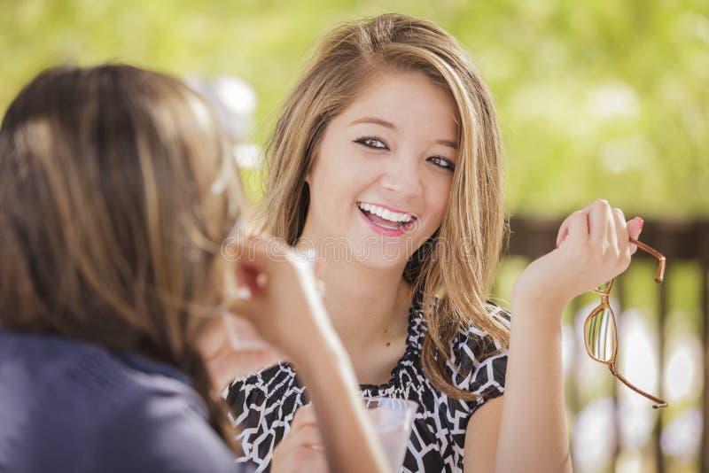 Attraktiva flickvänner för blandat lopp som utanför talar över drinkar royaltyfri bild