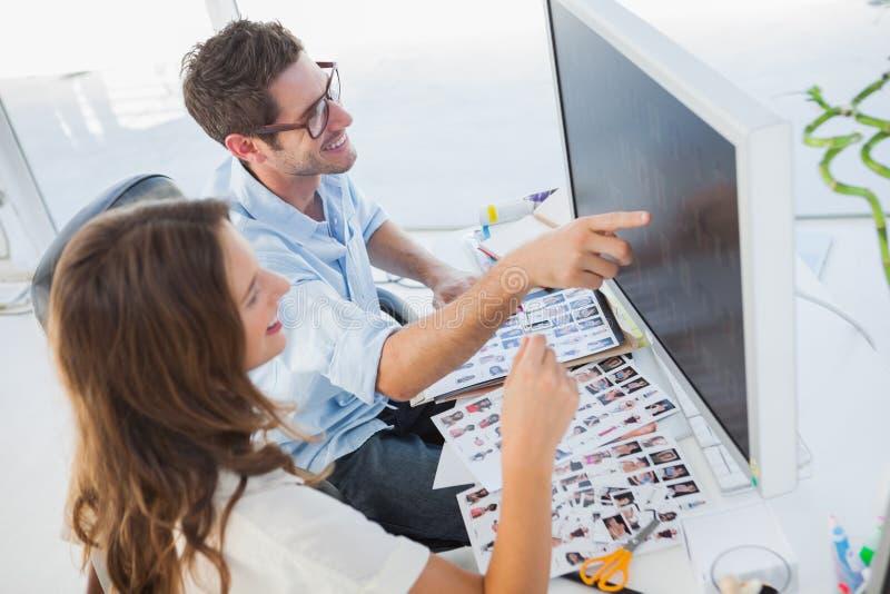 Attraktiva fotoredaktörer som arbetar på datoren royaltyfri bild