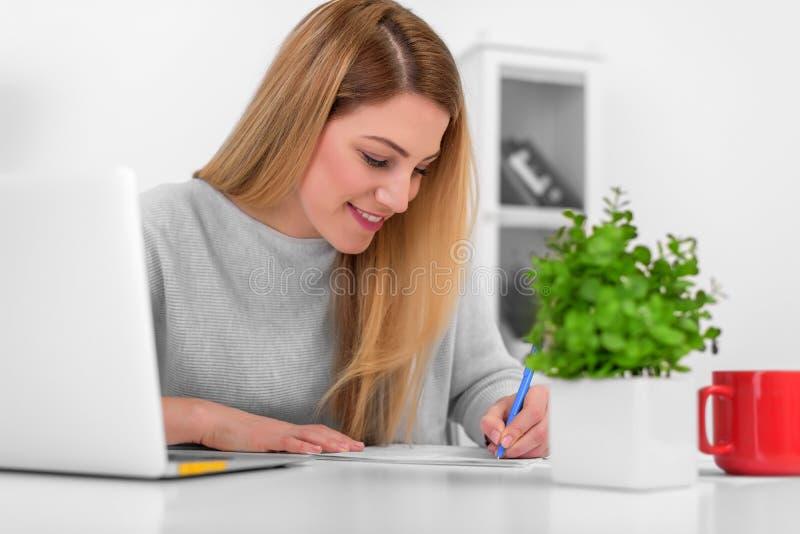 Attraktiva godlynta arbeten för ung kvinna med dokument i kontoret eller hemma Skriver påfyllningslegitimationshandlingar på skri arkivfoton