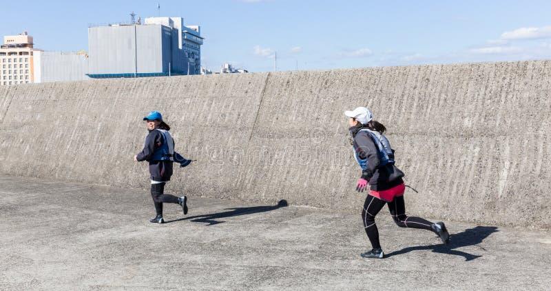 Attraktiva japanska flickor kör och ler arkivfoton